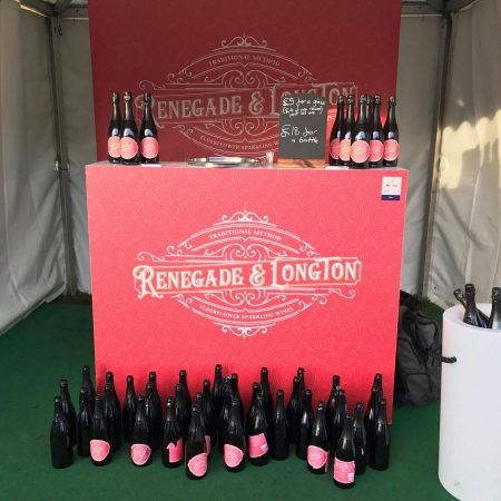 Red bar unit with lots of empty bottles of renegade and longton rhubarb sparkling wine in front of it