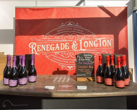 Brass bar top with six bottles of Renegade and Longton pure elderflower wine and six bottles of Renegade and Longton Blush elderflower and rhubarb wine