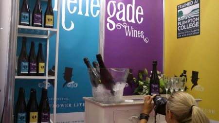 Photographer taking a photo of Renegade and Longton stand at a trade show with elderflower sparkling wine bottles in a cooler