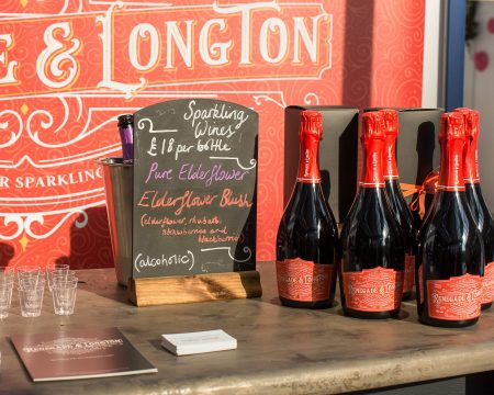 Brass bar unit top with bottles of Renegade and Longton blush elderflower and rhubarb sparkling wine beside a chalkboard sign at a food and wine festival
