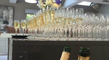 Champagne glasses lined up to be filled with sparkling wine for wedding toasts