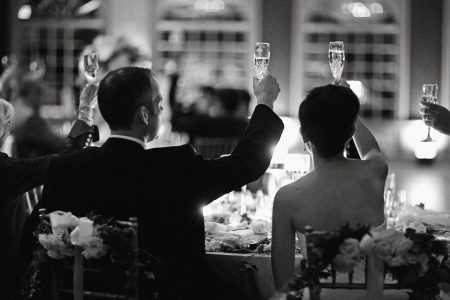 Bride and groom raising a glass of sparkling wine for the wedding toasts