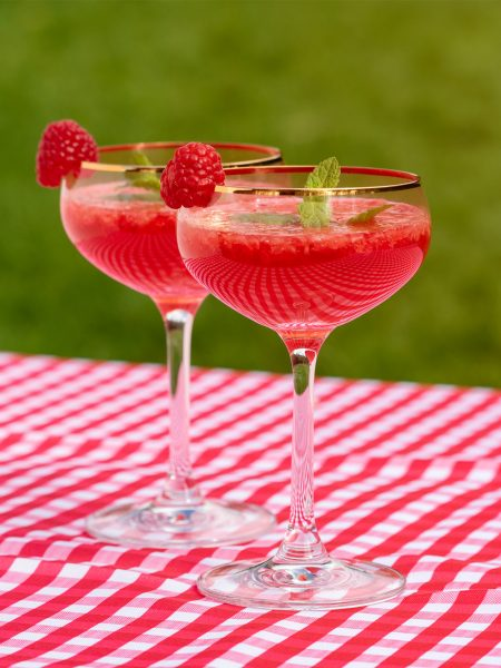 Close up of two coupe glasses filled with a Raspberry fizz vegan cocktails