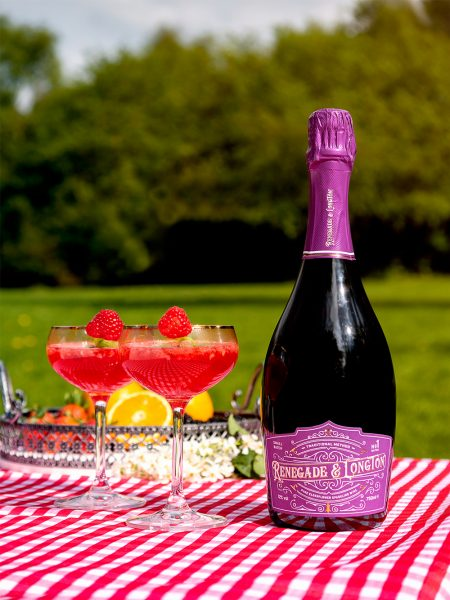 One bottle of Renegade and Longton pure elderflower sparkling wine beside two coupe glasses of Raspberry fizz vegan cocktails
