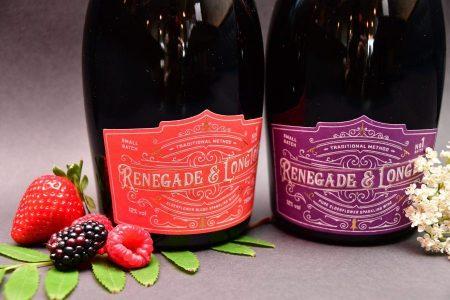 Bottle of Renegade and Longton blush elderflower and rhubarb sparkling wine beside berries and bottle of pure elderflower sparkling wine beside elderflower flowers