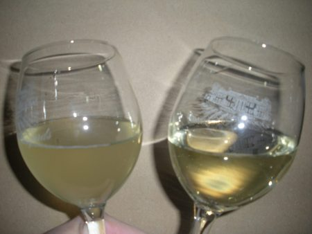 Two glasses of sparkling wine one that is clear and the other cloudy