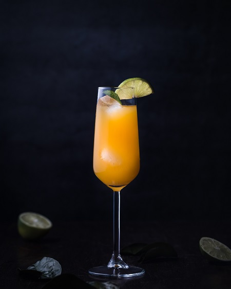 Champagne flute glass filled with a Mimosa made with Elderflower sparkling wine