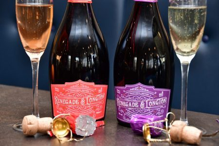 Two Renegade and Longton Sparkling Wine Bottles with full glasses one of pure elderflower sparkling wine and the other blush elderflower and rhubarb sparkling wine