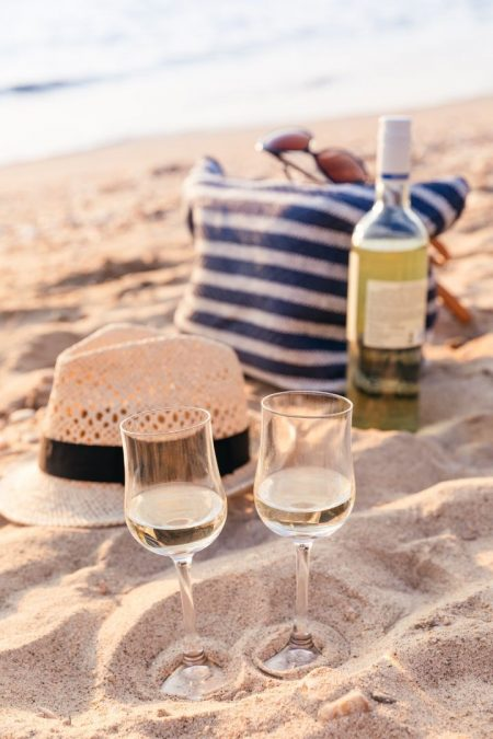 Two glasses of white wine on the beach with an open bottle, hat and striped bag behind them