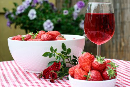 One large and one small bowl of strawberries with a glass of rhubarb wine