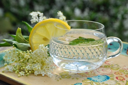 Seethrough mug being used to serve warm elderflower cordial garnished with a lemon