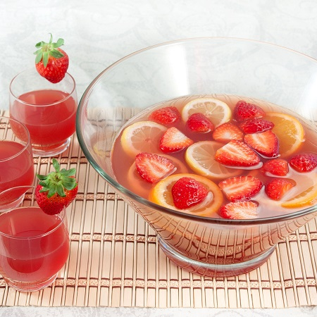 Punch summer cocktail served in a big bowl filled with strawberries