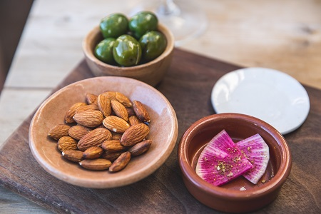 Small bowls of almonds and olives to paired with elderflower wine