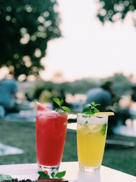 Two glasses of summer cocktails in a city park one red and the other yellow