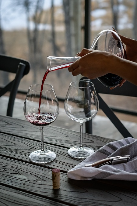 Red wine being poured into a wine glass from a decanter